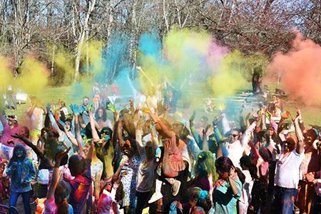 A crowd of people throw colorful paints during a Holi celebration and Lake Sammamish State Park in I