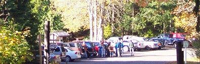 Park entrance crowded with visitors parking in front of fall-colored trees