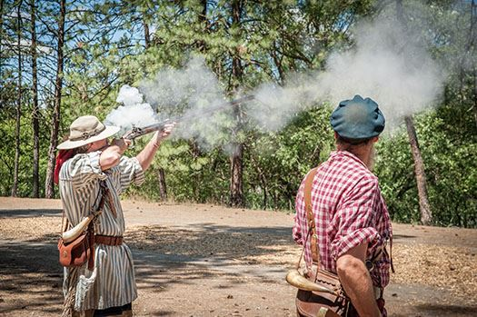 Riverside reenactment, man shooting gun, smoke in the air