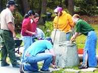 A crew of brightly clothed volunteers working to clean a water fountain