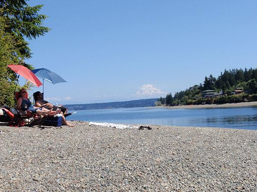 Eagle Island, couple sitting on beach, water and mount rainier in background